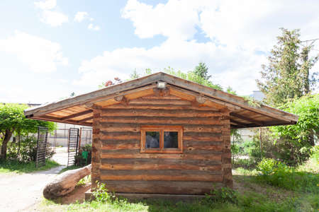Wooden house in the forest for relaxation. Small resort wooden house. Wooden hut in a pine forest.