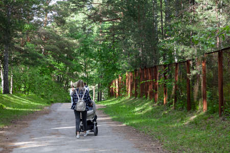 Back view of mother walking with her baby in stroller. Gray stroller outside. Young modern mom with baby son in stroller walking in Sunny Park. Concept of the joy of motherhood and summer mood
