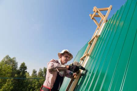 Construction elderly worker install new roof, Roofing tools, Electric drill used on new roofs with Metal Sheet.