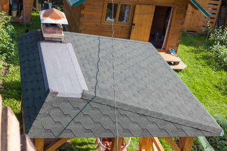 Modern roofing and decoration of chimneys. Flexible bitumen or slate shingles. House with a roof from a bituminous tile.