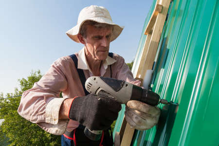 Construction elderly worker install new roof, Roofing tools, Electric drill used on new roofs with Metal Sheet. Self-made house by retired man. Stock fotó