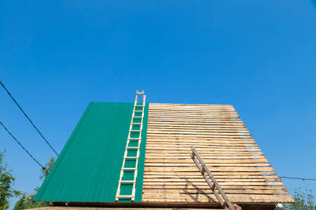 Construction industry. Timber framework of greenhouse roof trusses with scaffold on a building being built on a new housing estate. Roofing construction house Stock fotó