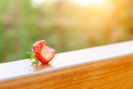 Red strawberry beautiful that are bitten on the wooden beam Stock fotó