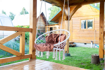 Round swinging chair in the gazebo outdoors. Summer