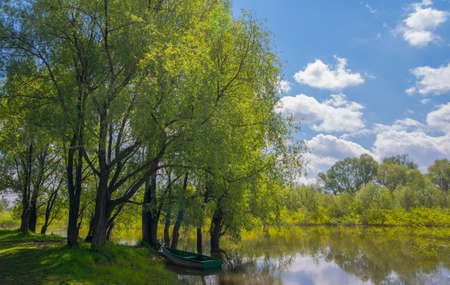 made russia: Wooden boat on the river near the tree