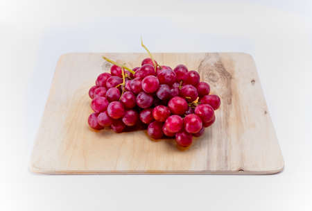 shinning leaves: The branch of red grapes lies on a wooden board on a white background