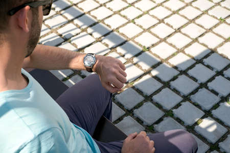 A man looks at his watch in the street an a day light