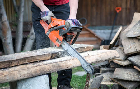off cuts: Man cuts off the board chainsaw outdoors in summer