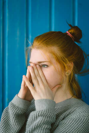 alertness: Red-haired girl put her hands on his nose against a blue wall. Redhead. Excitement. Pain. Alertness. Stock Photo