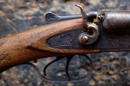 gatillo: Disparar un rifle de caza de edad en un fondo de madera durante el día