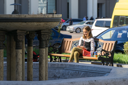 Tbilisi, Georgia-SEP 25, 2016: the girl with the phone sits on the bench at liberty square
