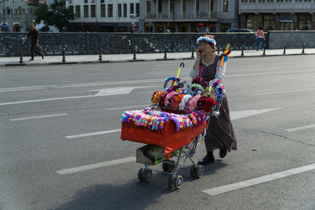TBILISI, GEORGIA-SEP 25, 2016: Saleswoman of the wreaths is on the road pushing a shopping trolley with goods.