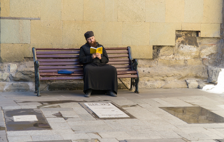 TBILISI, GEORGIA-SEP 25, 2016: Georgian priest reading a book sitting on a bench Editorial
