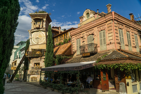TBILISI, GEORGIA - SEP 25, 2016: The leaning clock tower of Rezo Gabriadze Marionette Theatre with the art cafe from the right.