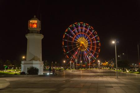 BATUMI, GEORGIA - OCT 7, 2016: Night view of Batumi. Ferris wheel and lighthouse on seaside boulevard.