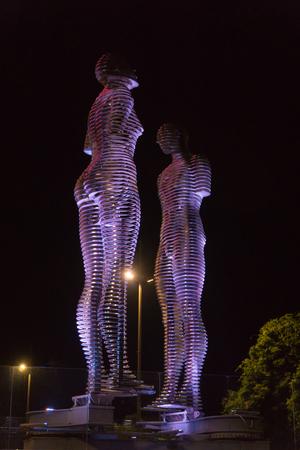 BATUMI, GEORGIA - OCT 7, 2016: Moving metal sculpture Ali and Nino by Tamara Kvesitadze and Ferris wheel in the everning. Editorial