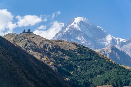 View of village Stepantsminda, Gergeti Trinity Church and mount Kazbek in Sunny weather Standard-Bild