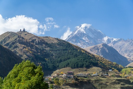 View of village Stepantsminda, Gergeti Trinity Church and mount Kazbek in Sunny weather Banco de Imagens