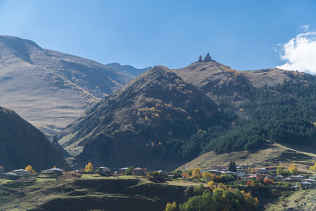 View of village Stepantsminda and Gergeti Trinity Church in sunny weather Banco de Imagens