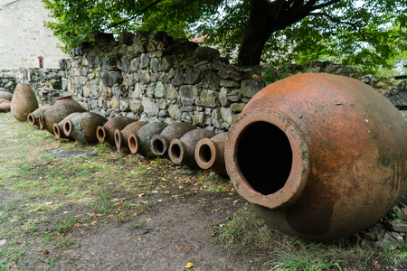 Old traditional wine jars, called Kvevri, lined in a row, by a monastery in Telavi, Georgia.