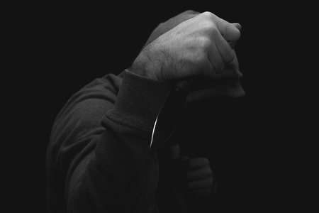 a man in a jacket with a hood hiding his face with a knife in his hand on a black background