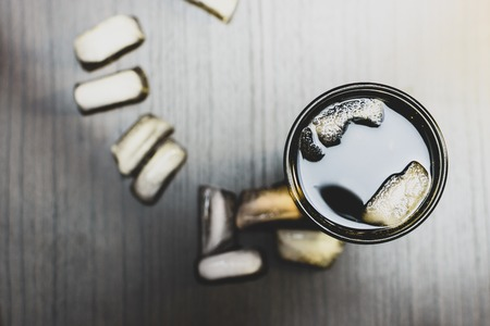 dark fizzy sweet drink in a glass with ice on a dark woody background