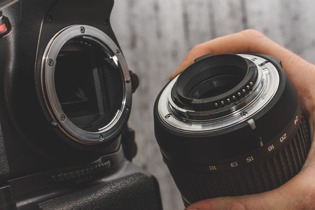 the photographer attaches the lens to the SLR camera