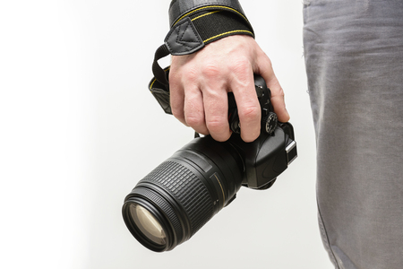 photographer with a reflex camera and a telephoto lens on a light background