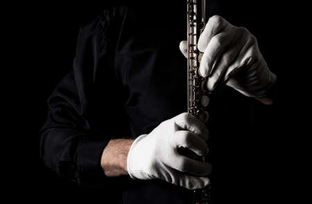 flutist in a black shirt, against a dark background .. male executor on a wooden wind instrument Фото со стока
