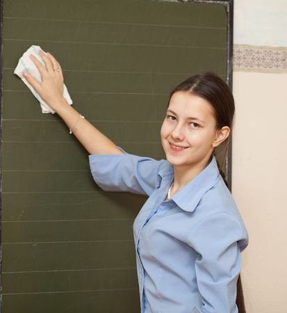 Girl high school girl washes the chalkboard Stock Photo - 8132610