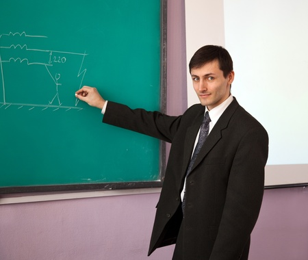 Young scientist giving a lecture on the background of the chalkboard with the scheme.