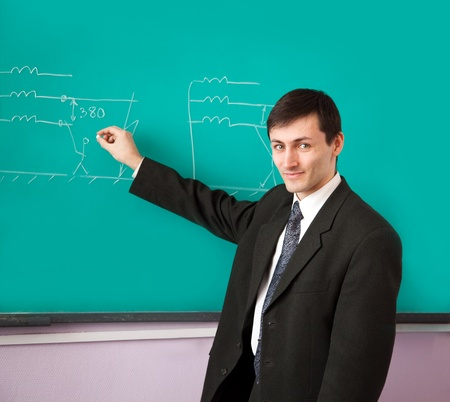 Young scientist giving a lecture on the background of the chalkboard with the scheme. Stock Photo - 9091227