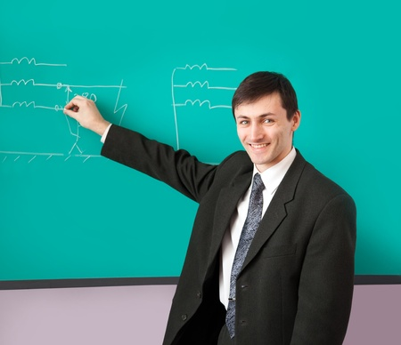 Young scientist giving a lecture on the background of the chalkboard with the scheme. Stock Photo - 9091225