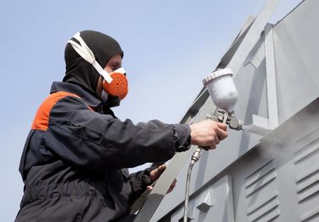 sprayer: A commercial painter on the stairs spray painting a steel exterior wall against the blue sky