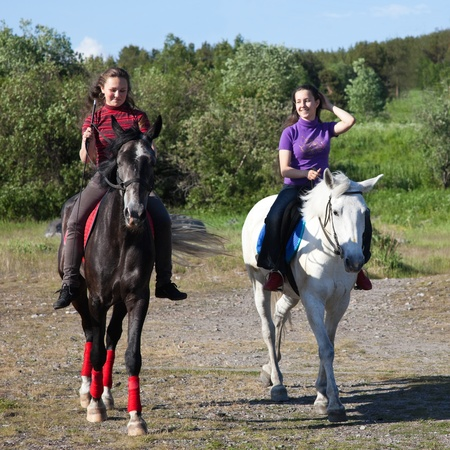 Two girls on horseback, on a clear sunny day photo