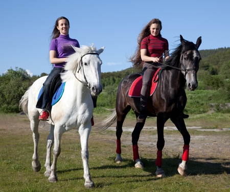 Two girls on horseback, on a clear sunny day