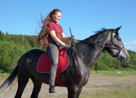 Una chica cabalgando en un caballo en una pradera Foto de archivo - 10605642
