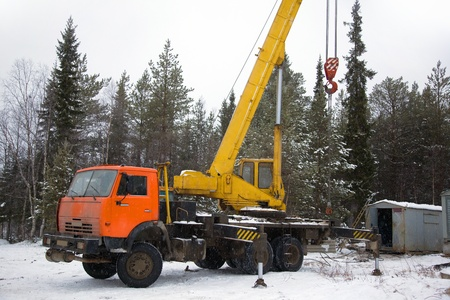 crane working in the woods in winter. The snow. Taiga.