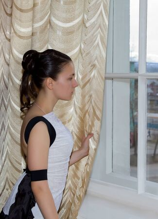 A girl in a ball gown standing by the window and looks at the street photo