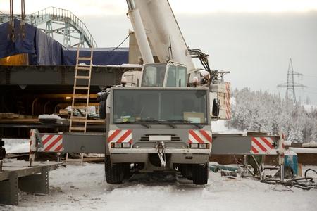 100 ton crane at the construction of the bridge. The snow. Taiga.