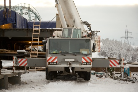 100 ton crane at the construction of the bridge. The snow. Taiga.