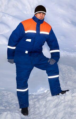 Trabajador en el traje de invierno que consiste en una chaqueta y pantal�n en el contexto de la nieve Foto de archivo - 12325684