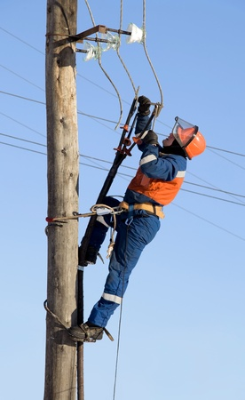 Electrician in blue overalls working at height photo