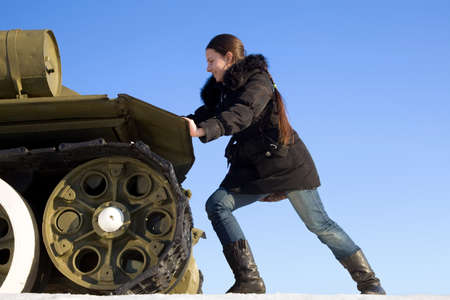 pushes: The girl pushes the tank monument on the background of blue sky