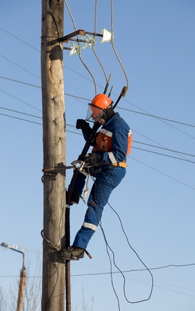 Electrician in blue overalls working at height with wires Stock Photo