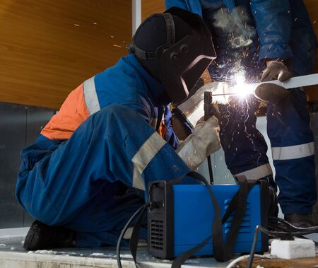 A welder working in a metal structure in the room