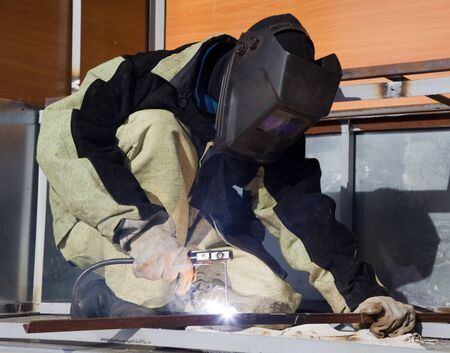 Welder in a special suit, while working in direct sunlight photo