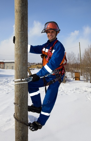 Electrician on a pole in a good mood against the backdrop of snow and bright sunshine Stock Photo
