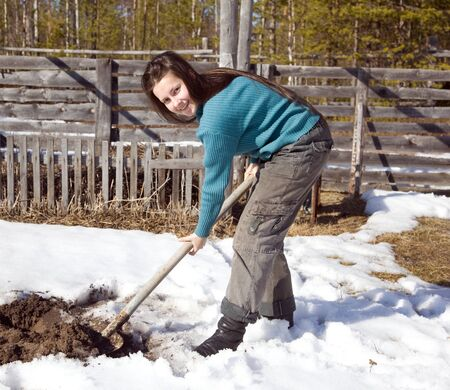 A young girl digs the garden in early spring. Russia. The extreme north. photo