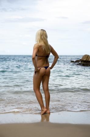 Beautiful slim blonde on the beach. back view